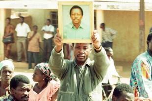 Un homme brandit la photo du journaliste Norbert Zongo lors de ses funérailles à Ouagadougou, Burkina, 16 décembre 1998.