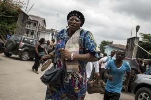 © John Wessels, AFP Une femme court après des tirs de sommation de la police devant la cathédrale de Kinshasa, le 12 janvier 2018.