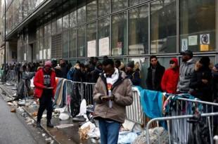 Des migrants font la queue pour déposer leur demande d'asile, à Paris, le 21 décembre. THIBAULT CAMUS / AP