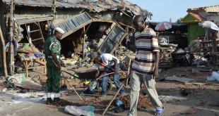 Un homme marche à travers Maiduguri, dans le nord-est du Nigeria, après qu'une jeune femme se soit fait exploser dans la rue, tuant une vingtaine de personnes, le 21 juin 2015. Crédit : STRINGER / AFP