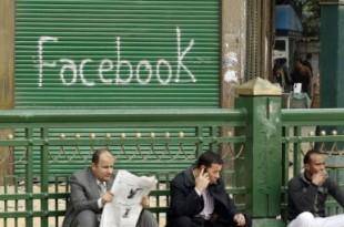 Des Égyptiens assis devant un graffiti «Facebook» lors de manifestations sur la place Tahrir au Caire en février 2011. © REUTERS / Dylan Martinez