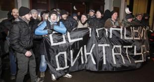 Des manifestants de l'opposition russe brandissent une banderole disant «arrêtez la dictature» lors d'un rassemblement anti-gouvernemental devant le Comité central des élections au centre-ville de Moscou, en Russie, le 14 février 2012.