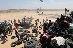 Des palestiniens manipulent des pneus destinés à être brûlés afin de fournir un rideau de fumée protecteur face à l'armée israélienne, le 15 mai 2018 à la frontière entre Gaza et Israël. © REUTERS/Ibraheem Abu Mustafa
