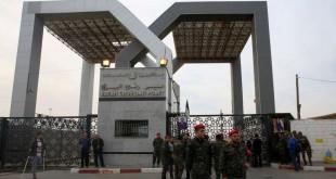 Des agents de sécurité du Hamas montent la garde devant la porte principale du poste frontalier de Rafah tandis que des passagers traversent la frontière égyptienne, à Rafah, dans la bande de Gaza, le 18 novembre 2017.