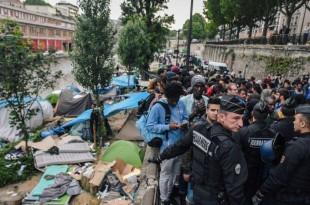 Les policiers anti-émeutes évacuent un camp de réfugiés le long du canal de Saint-Martin au Quai de Valmy à Paris.
